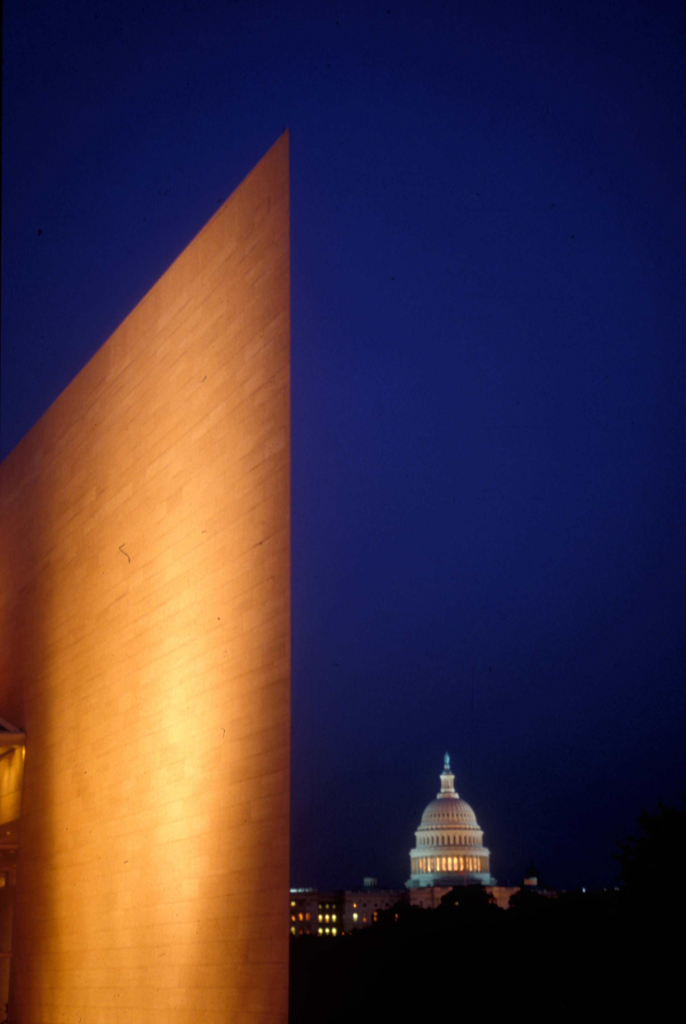 """A view of the National Gallery of Art East Building and U. S. Capitol dome at night. The """"knife edge,"""" signature southwest corner of the East Building, cleaves the air at 19.5 degrees to a height of 116 feet. It may be the sharpest corner of any building in the world. Photo © Dennis Brack/Black Star. National Gallery of Art, Washington, Gallery Archives"""