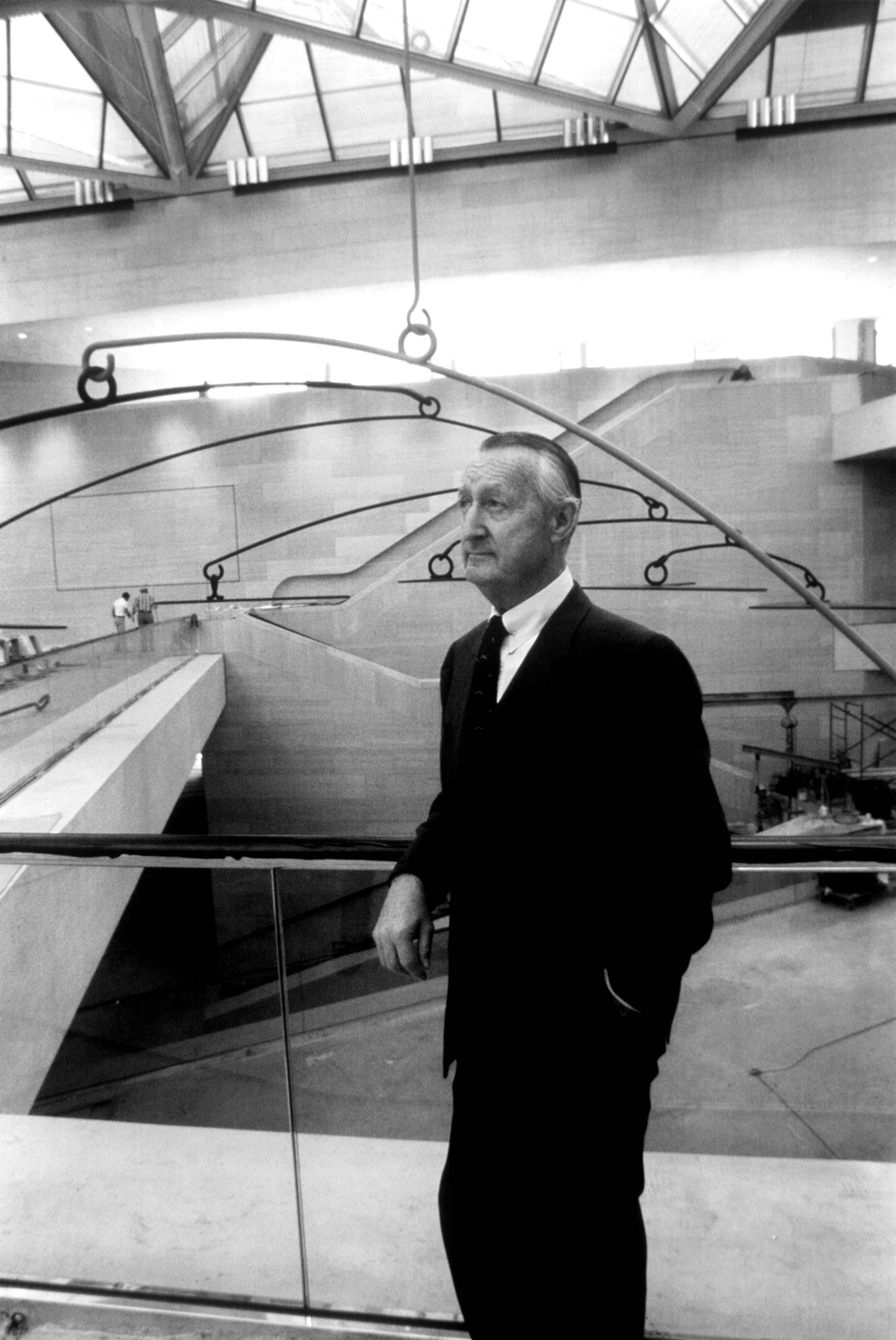 Paul Mellon on the East Building Mezzanine in front of Alexander Calder's Untitled (1976). © Dennis Brack/Black Star. Courtesy of the National Gallery of Art, Washington