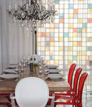 The acrylic Philippe Starck Ghost chairs, a gauzy curtain, a 1950s wall of colored glass, and a vintage chandelier provide contemporary glamour at the waterfront Río Mar.