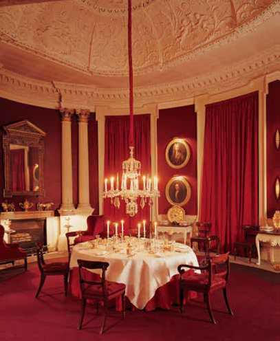 The dining room, converted from the original chapel; real candles burn in the chandelier. Under the starched white tablecloth is red damask that matches the painted walls and thick curtains.