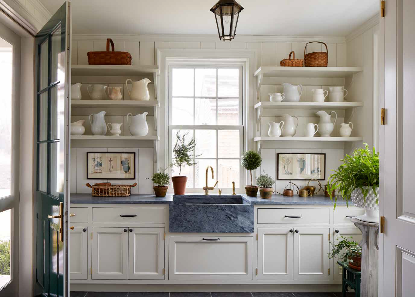 P. 196-197 Open shelves and ample counter space permit the display of three collections in this generously scaled mudroom: earthenware pitchers, brass watering cans, and wicker baskets. Photo Credit: William Abramowicz/Art + Commerce
