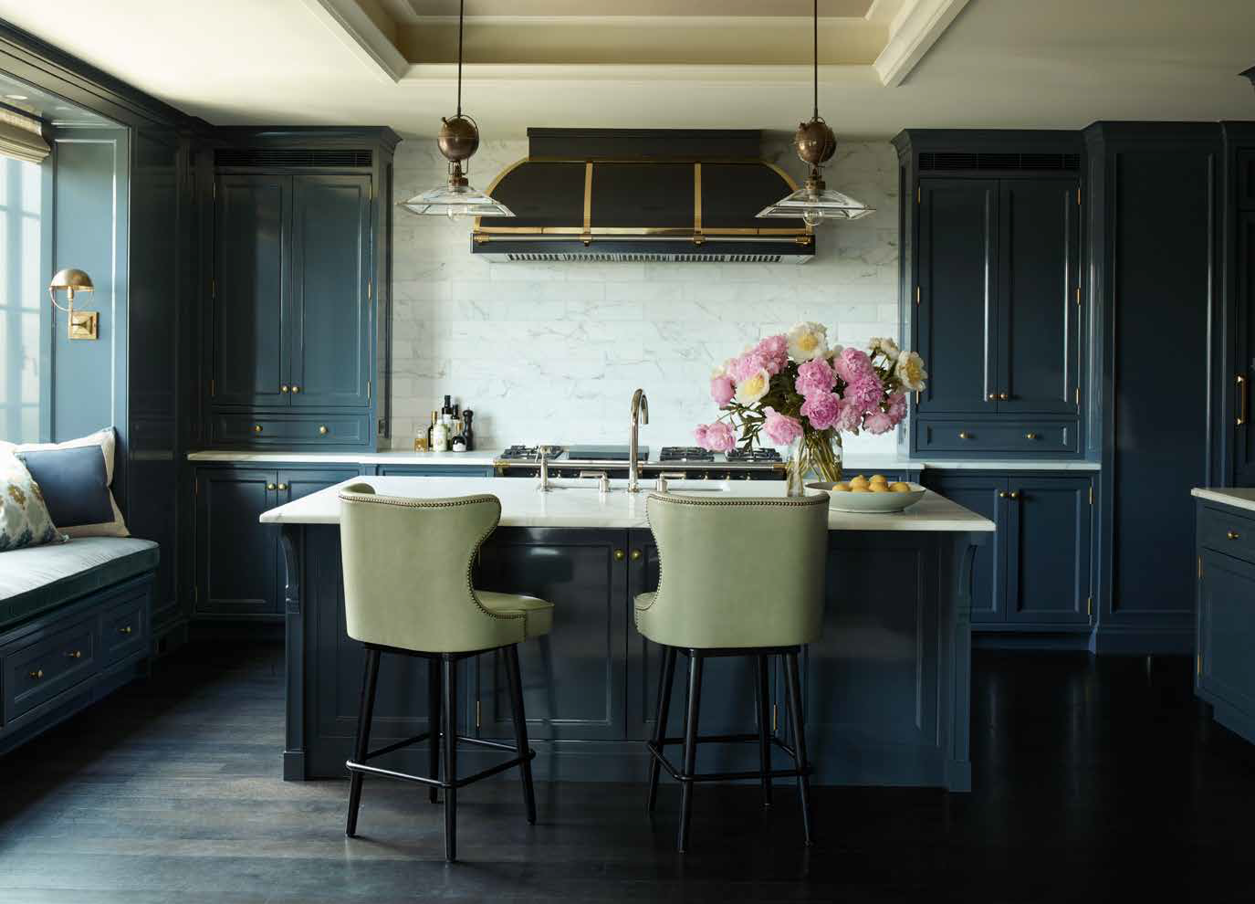 p. 22-23 The austere elegance of this kitchen—its simple, symmetrical architectural elements, careful alignment of marble countertops, and rich blue lacquerwork— is softened by the curvaceous profile of the barstools and inviting window seat. Photo Credit: Simon Upton