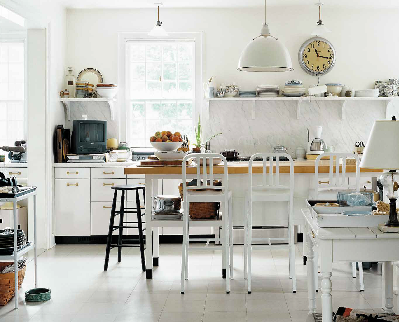 While this kitchen might appear to be a random cornucopia at a glance, certain elements suggest a distinct narrative character: the Emeco stools, the laboratory pendant light, the schoolroom clock, and, not least, the chunky vintage TV. I see a cafeteria in a scientific research facility, circa 1980. Not everyone would, but that invitation to interpret gives this kitchen character. Photo Credit: Laura Resen