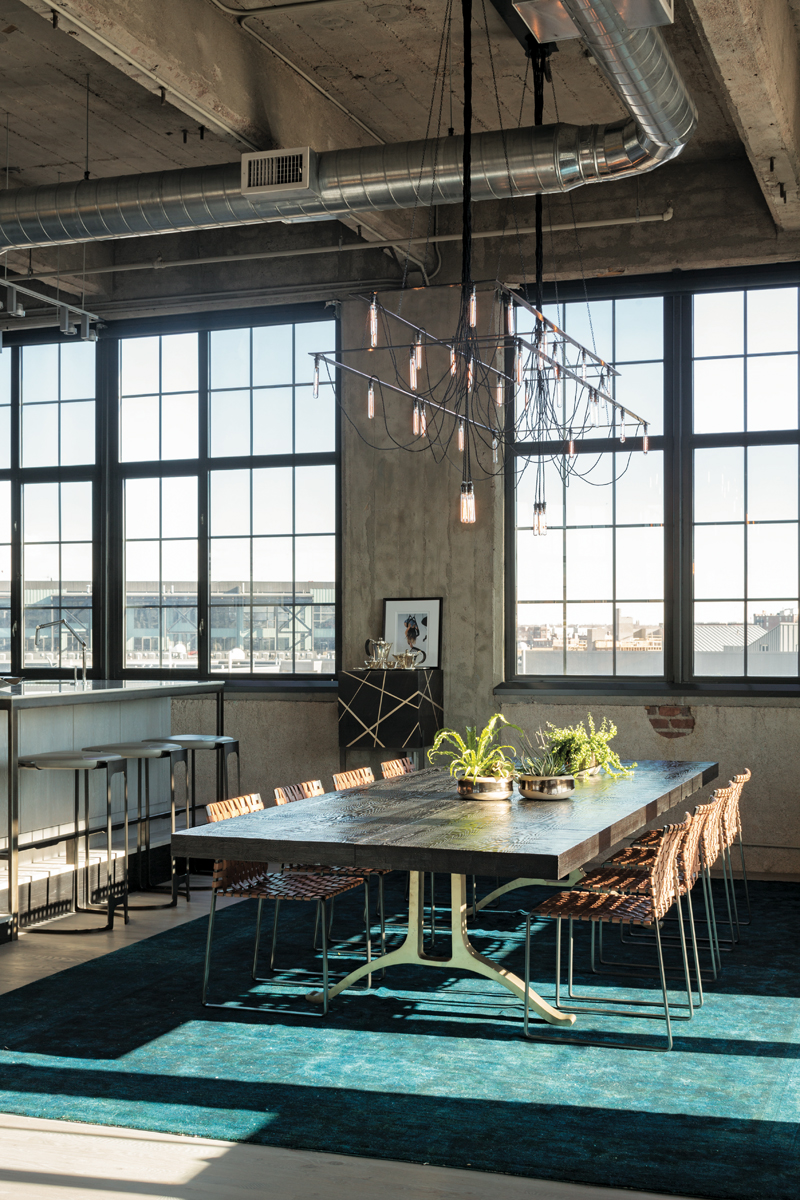 The open-plan loft is ideal for entertaining, and the dining area is marked out by a deep-teal rug and an industrial-style chandelier. Photo by David Lauer