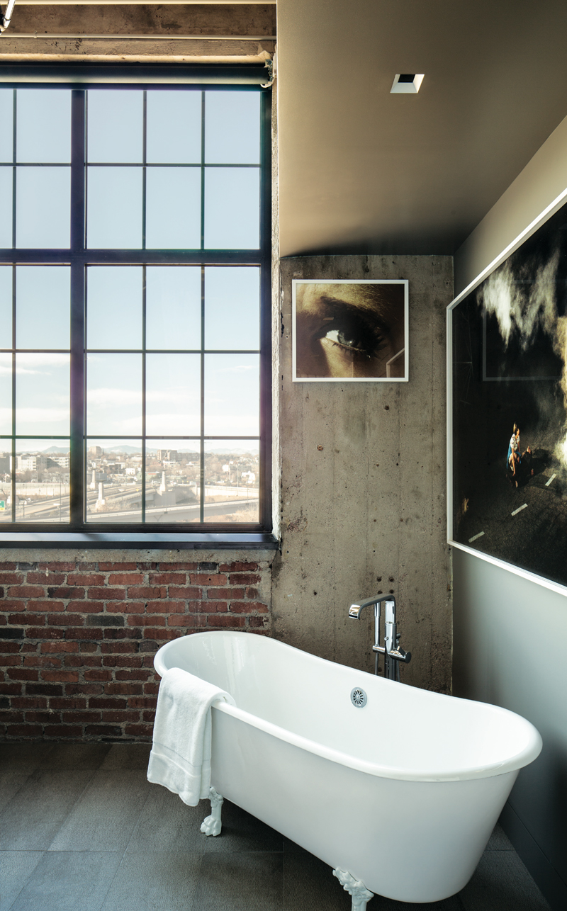 A freestanding vintage clawfoot bath with modern faucet sits in front of an enormous black-framed window. Photo by David Lauer