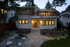 Back of two story stucco house with metal roof and stone patio