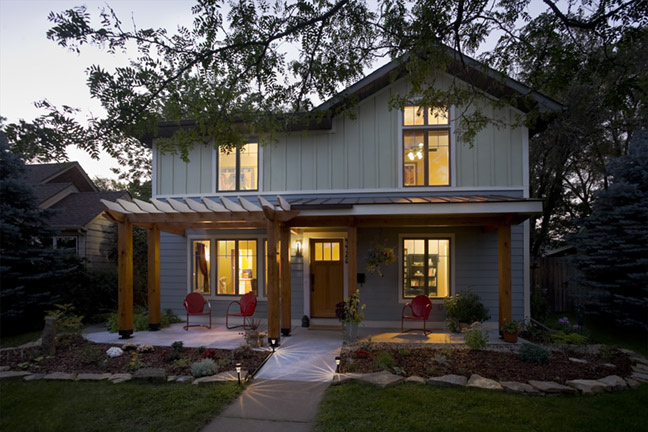 Front of remodeled house showing covered patio, arbor and landscaping at dusk