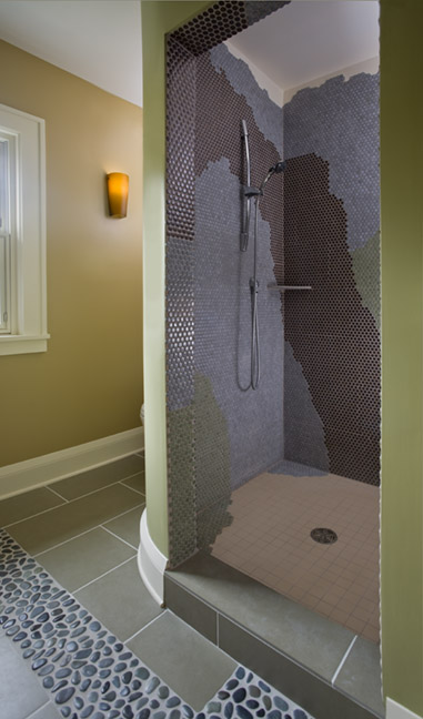 Walk-in shower with round mini tiles arranged in organic shapes by color