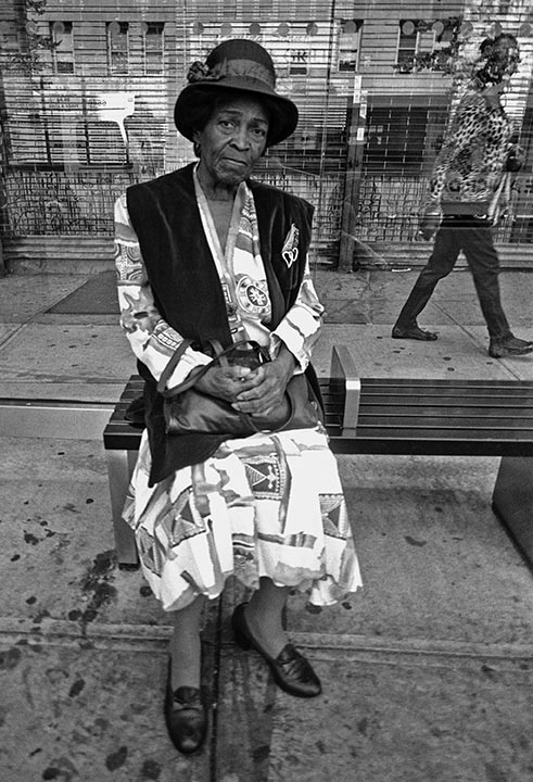 Older Woman sitting at bus shelter72