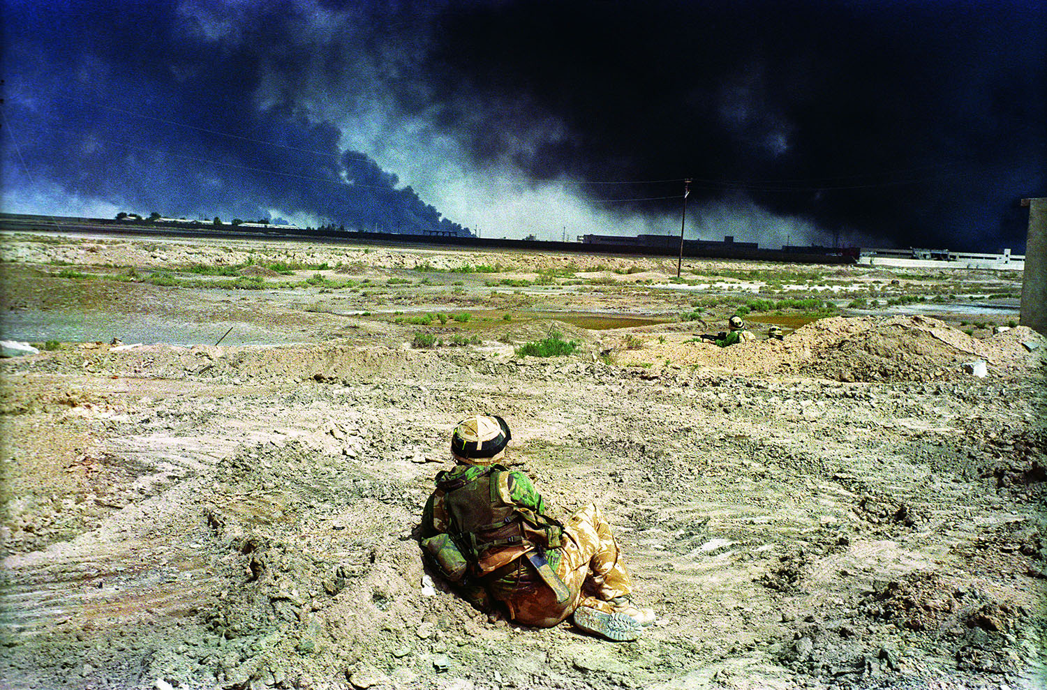Correct Caption:BASRA, IRAQ: 7 April 2003British soldiers watch black smoke rising from Basra. The building on the right, a technical college, was hit repeatedly by British fire in response to Iraqi sniper attacks.PHOTOGRAPH by ALAN CHIN