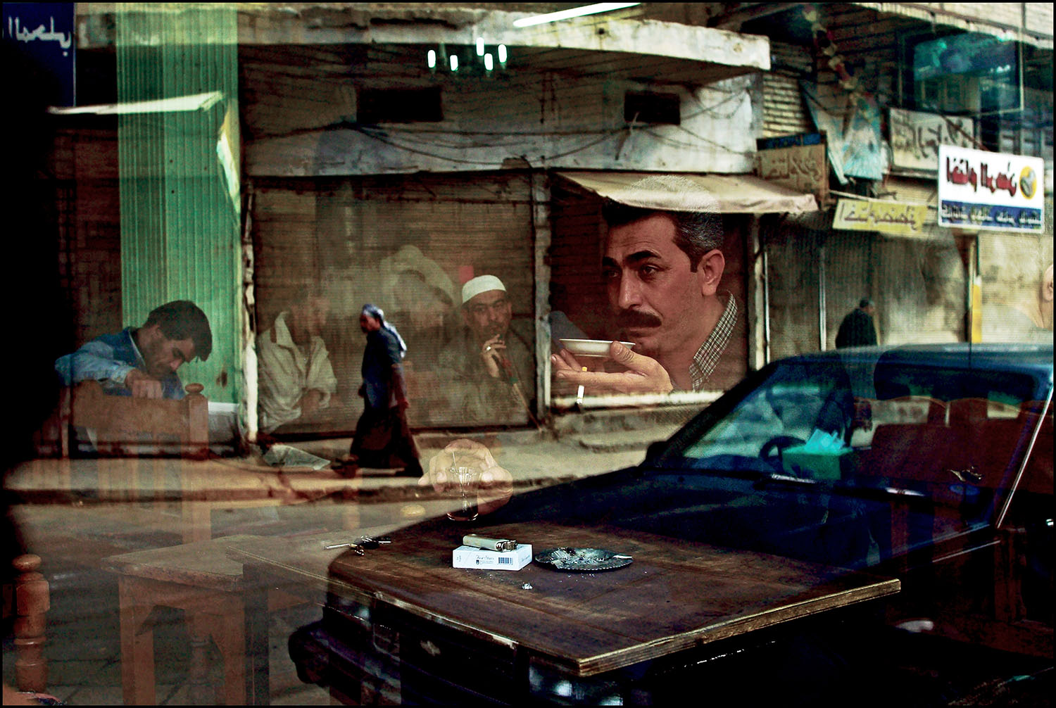 Correct Caption:Baghdad February 12, 2003. Six weeks before the start of the war, a man sits drinking tea at the Al Zahawi cafe on Rashid Street. Cafes are a trademark of this ancient city, gathering places where men play dominos, blackjack and socialize. Photo by Bruno Stevens