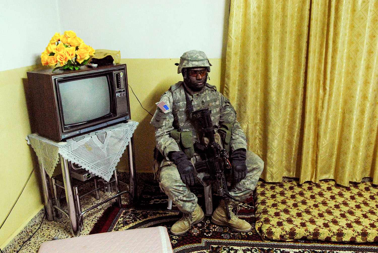 Correct CaptionRawah, IraqMarch, 2006 A weary American soldier stands guard as a residential home is searched. Peter van Agtmael/Magnum